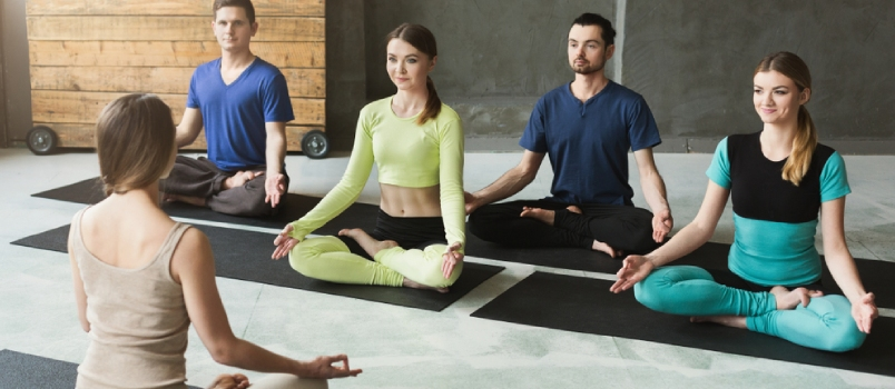 Yoga Teacher And Beginners In Class, Making Asana Exercises. Lotus Pose